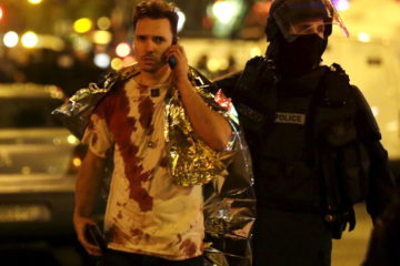 AFrenchpolicemanassistsablood coveredvictimneartheBataclanconcerthallfollowingattacksinParis,France